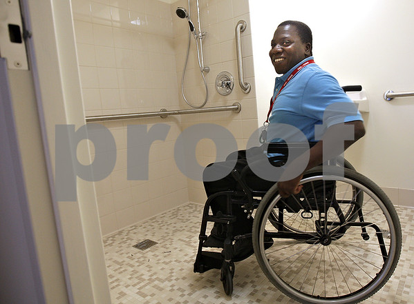 Monica Maschak - mmaschak@shawmedia.com<br /> Houndsro Adjegan, a resident since 2010, takes a peek at a newly renovated ADA compliant room in the Golden Years Plaza in DeKalb on Thursday, August 8, 2013. The DeKalb Housing Authority is wrapping up a two-year $2 million project to renovate Golden Years Plaza and various equipment. Adjegan will be moving into one of these newly renovated rooms in less than two weeks.