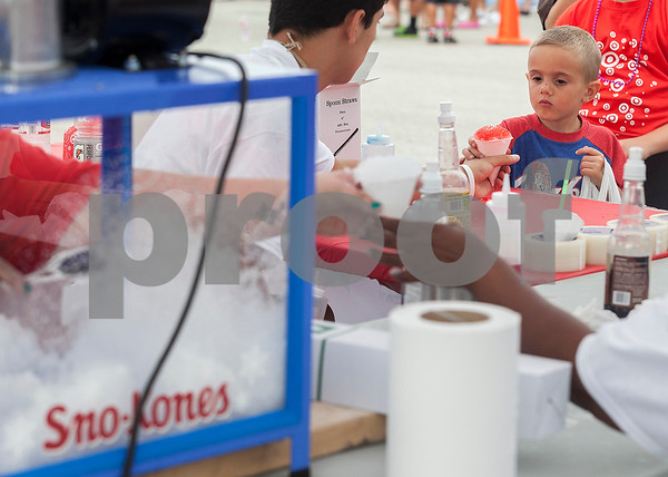 Erik Anderson - For the Daily Chronicle <br /> Target volunteer Mikie Lozano (left) hands a snow cone to Wes Young, 4, during the National Night Out held at the Target parking lot in DeKalb on Tuesday, August 6, 2013. The event promoted self-defense through demonstration of events including a police K-9 dog.