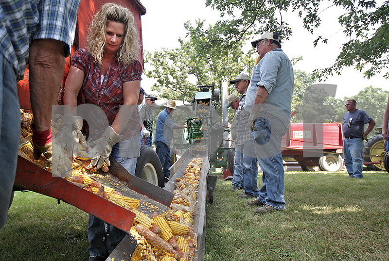 Monica Maschak - mmaschak@shawmedia.com<br /> Stephanie spaces out the amount of corn falling onto the belt of a John Deere Corn Sheller at the opening day of the annual Threshing Bee in Sycamore on Thursday, August 8, 2013. A corn sheller separates the kernels and husk from the cob.