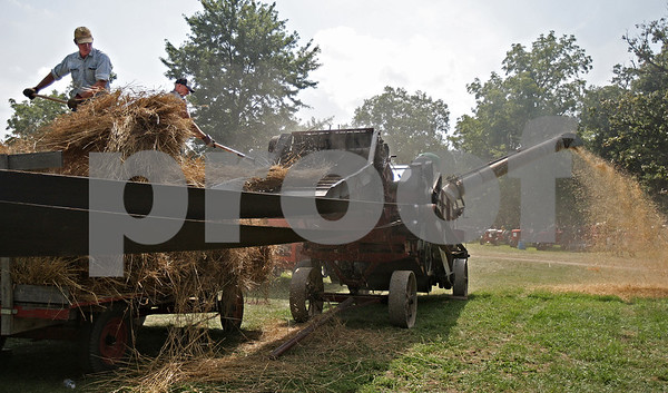 Monica Maschak - mmaschak@shawmedia.com<br /> Brian Atkinson and his son, Nicholas Atkinson, pitch bundles of wheat into a Minneapolis Threshing Machine at the opening day of the annual Threshing Bee in Sycamore on Thursday, August 8, 2013.