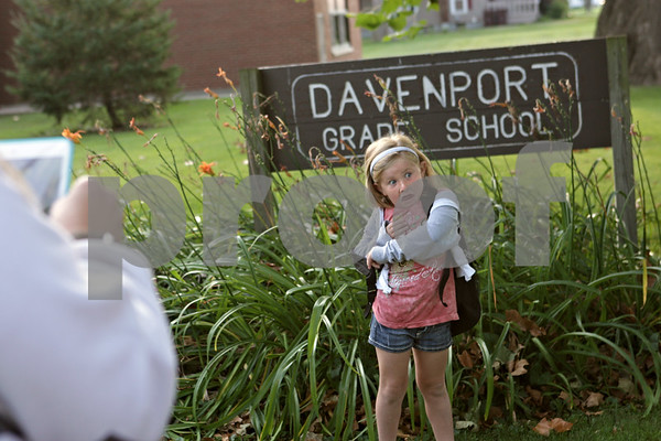 Rob Winner – rwinner@shawmedia.com<br /> <br /> Madi Pasholk, 5, struggles to get her backpack off as her mother, Allison Pasholk, waits to take a photograph with a tablet outside Davenport Elementary School in Genoa, Ill., for the first day of school for kindergartners on Friday.