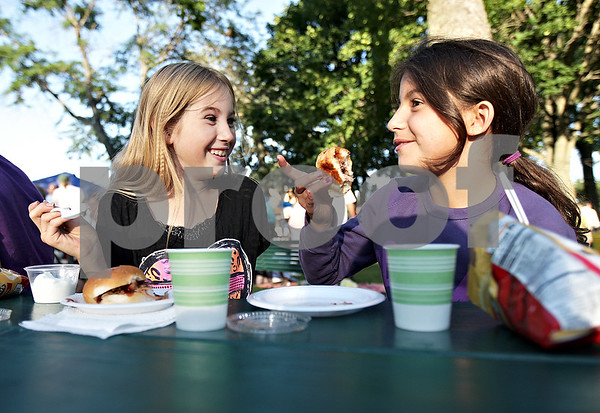 Monica Maschak - mmaschak@shawmedia.com<br /> Lilly Murphy, 9, and Sofia Bellafiore, 10, enjoy their ice cream and mini pork sandwiches at the Hinckley Business Association's annual free ice cream social at Pioneer Park in Hinckley on Tuesday, August 13, 2013. Sandwiches and ice cream were provided by South Moon Barbeque and Dairy Joy respectively.