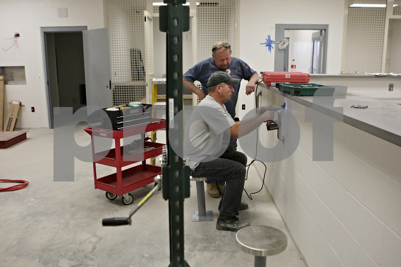 Rob Winner – rwinner@shawmedia.com<br /> <br /> Two workers install bars on a wall in the jail area of the new DeKalb police station located on Lincoln Highway on Monday, Aug. 12, 2013.