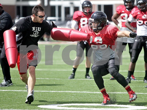 Monica Maschak - mmaschak@shawmedia.com<br /> Wide receiver Johnny Eagan fights for position around an assistant coach in a wide receivers drill during a practice at Huskie Stadium on Tuesday, August 13, 2013.