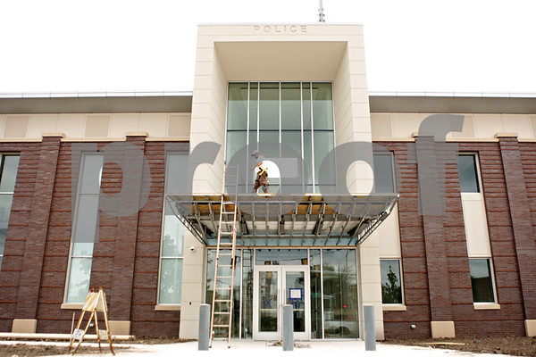 Rob Winner – rwinner@shawmedia.com<br /> <br /> A worker is seen on top of an overhang at the front entrance of the new DeKalb police station located on Lincoln Highway on Monday, Aug. 12, 2013. Unlike the current station the new structure has many windows allowing for natural light.