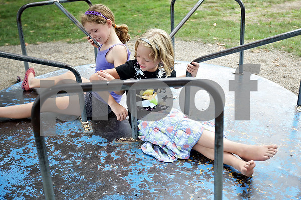 Monica Maschak - mmaschak@shawmedia.com<br /> Reagan Wesley, 10, and Taylor Wesley, 7, link arms while they spin on a merry go round at the Cortland Summer Fest on Saturday, August 10, 2013.