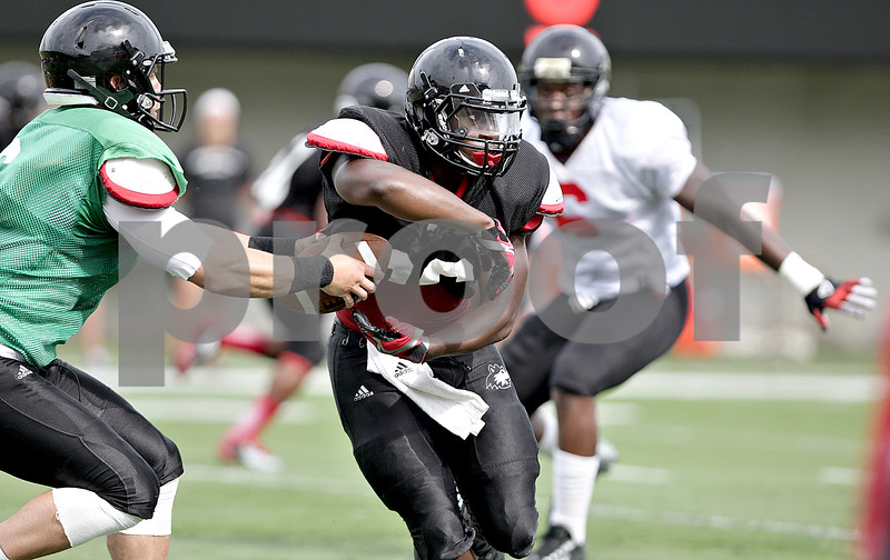 Monica Maschak - mmaschak@shawmedia.com<br /> Running back Keith Harris Jr. prepares for the hand-off during a practice at Huskie Stadium on Friday, August 9, 2013.