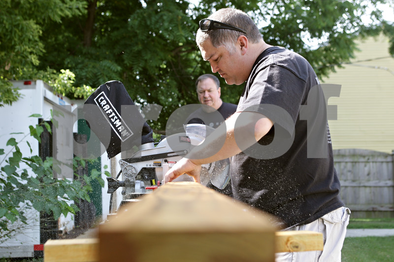 Rob Winner – rwinner@shawmedia.com<br /> <br /> Chris Lamb (right) cuts a piece of wood as Dennis Obenchain watches as the two helped construct a bicycle rack for Pine Acres Rehab & Living Center in DeKalb as part of the Craftsman Make a Difference Tour on Thursday, Aug. 15, 2013.
