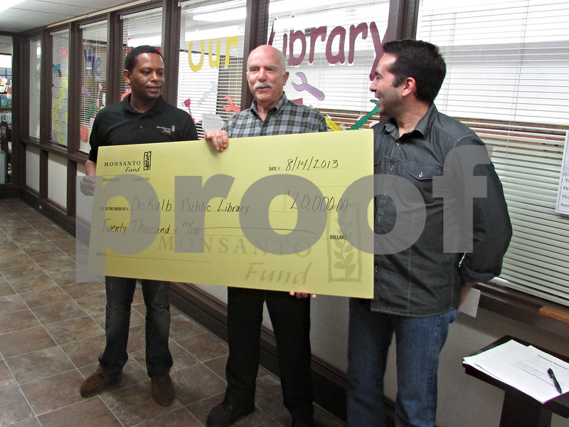 Chris Burrows – cburrows@shawmedia.com<br /> <br /> Clark Neher (center), the President of the DeKalb Library Board of Trustees, accepts a check for $20,000 from Ricky Vazquez (right) and Misiker Madefro (left) of the Monsant Fund at Wednesday's board meeting. The money will go towards the library's expansion project.