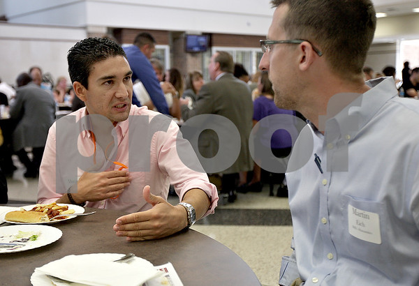 Monica Maschak - mmaschak@shawmedia.com<br /> Daniel Quijano (left), a new social studies teacher from Spain, speaks with Marty Eich, a new humanities teacher, at the 4th Annual New Teachers Welcome Event at DeKalb High School on Wednesday, August 21, 2013.