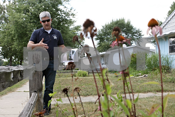 Rob Winner – rwinner@shawmedia.com<br /> <br /> Carl Leoni, the city of DeKalb's Crime Free Housing & Inspection Coordinator, inspects the lawn at a rental property located on the 400 block of Fairlane Avenue in DeKalb on Friday, Aug. 16, 2013. Leoni works with landlords to bring properties up to city code.