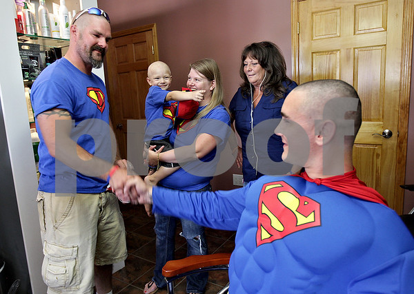 Monica Maschak - mmaschak@shawmedia.com<br /> Three-year-old Dylan Carey, held by mother Chris Carey, points excitedly at his idol, Superman (Tyler Hunt) as father Tim Carey shakes his hand at a shave-a-thon fundraiser for Dylan at Q Salon and Quinn's Grooming Parlour in Shabbona on Saturday, August 17, 2013. Last month Dylan was diagnosed with neuroblastoma.