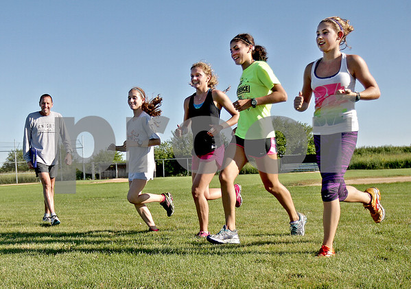 Monica Maschak - mmaschak@shawmedia.com<br /> (Left to right) Sophomore Brianna Bower, senior Sydney Strang, junior Jessica Kucera and junior Victoria Clinton run past Coach Doug Ecker at a Kaneland Cross Country practice on Wednesday, August 14, 2013.