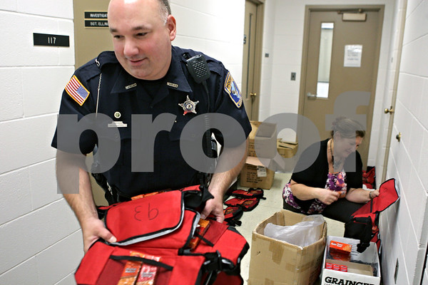 Rob Winner – rwinner@shawmedia.com<br /> <br /> On Tuesday morning within the Public Safety building on the campus of Northern Illinois University, Officer Marc Roccaforte (left) and office administrator Jennifer Jeffries pack about 100 cooler packs for NIU police officers that will be working on Thursday as students arrive for the fall semester. The packs will include snacks and drinks for the officers.