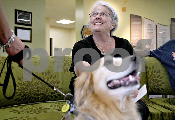 Monica Maschak - mmaschak@shawmedia.com<br /> Former cancer patient Suzy Allen pets Ever, a therapy golden retriever, in the waiting room of the Kishwaukee Hospital Cancer Center during the ice cream social on Thursday, August 22, 2013. Allen had come in for a three-year check up. The ice cream social was held for anyone whose family has been touched by cancer.