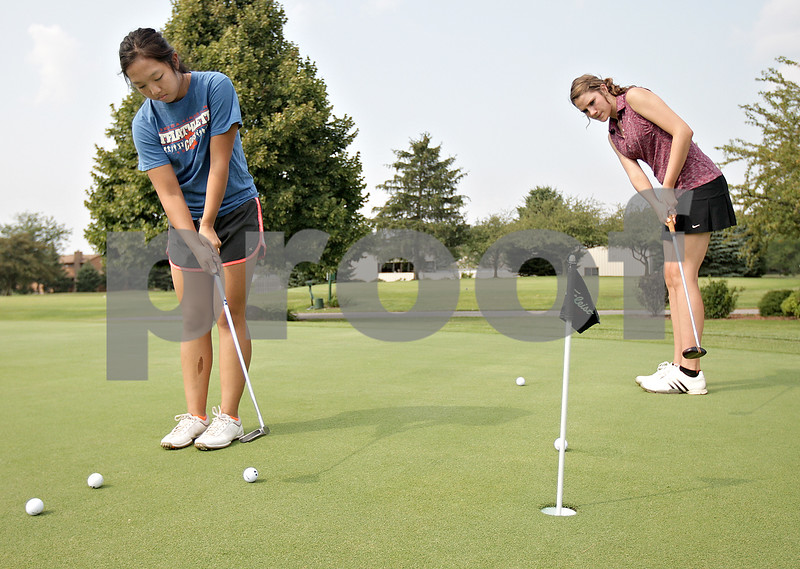 Monica Maschak - mmaschak@shawmedia.com<br /> Seniors Katie Thurlby (left) and Andrea Strohmaier practice putting during golf practice at Oak Country Club on Tuesday, August 20, 2013. Last year, the Genoa-Kingston girls won their regional championship.