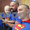 Monica Maschak - mmaschak@shawmedia.com<br /> Dylan Carey, 3, held by father Tim Carey, stares at his idol, Superman (Tyler Hunt), as they pose for a picture at a shave-a-thon fundraiser for Dylan at Q Salon and Quinn's Grooming Parlour in Shabbona on Saturday, August 17, 2013. Carey was diagnosed with neuroblastoma last month. All proceeds from the fundraiser went to the Carey family to offset medical costs.