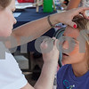 Erik Anderson - For the Daily Chronicle<br /> Ashley Rodriguez of Bethany Animal Hospital, paints the face of Oskar Boyce, 8, of DeKalb during the block party at the intersection of Somonauk Street and Elm Street in downtown Sycamore on Saturday, August 24, 2013.