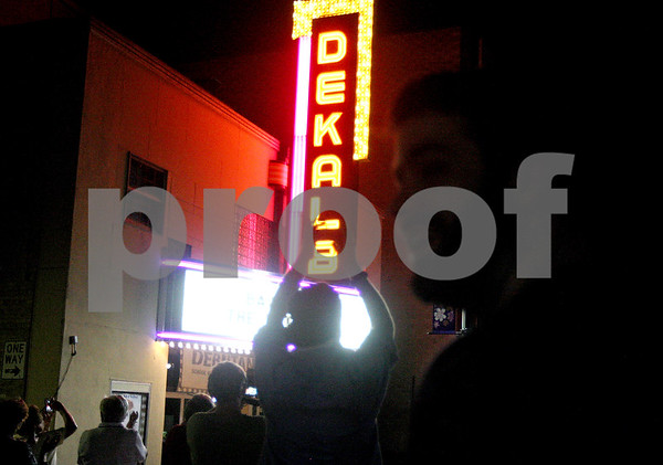 """Monica Maschak - mmaschak@shawmedia.com<br /> A crowd cheers when the word, """"DeKalb"""" appears in lights at a relighting ceremony to officially light the restored marquee of the former DeKalb Theatre, which now houses the Debutantes School of Cosmotology and Nail Technology, on Thursday, August 29, 2013. The theatre opened in March 1949, but the marquee has been dark since 1991 as several other businesses have operated there. DeKalb restored the marquee using TIF funds and Debutantes has promised to pay the operating costs."""
