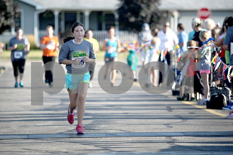 Monica Maschak - mmaschak@shawmedia.com<br /> Caitlin Krause, 12, of DeKalb, crosses the finish line at the annual Corn Classic 3 km and 10 km races on Saturday, August 24, 2013.