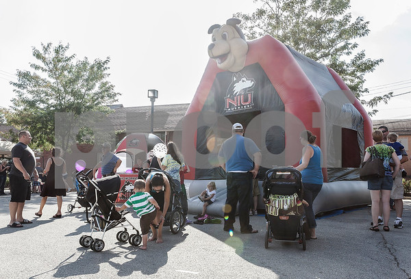 Erik Anderson - For the Daily Chronicle<br /> Families watch their kids in a bounce house set up by Northern Illinois University during the block party at the intersection of Somonauk Street and Elm Street in downtown Sycamore on Saturday, August 24, 2013.
