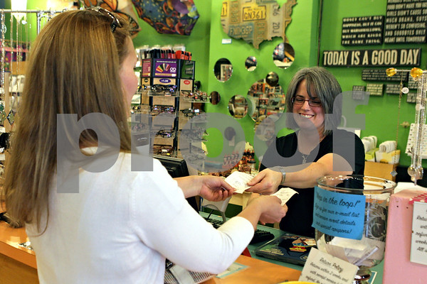 Rob Winner – rwinner@shawmedia.com<br /> <br /> After making a purchase at Moxie in DeKalb, Chrissy Large (left), of DeKalb, is handed her receipt by manager Courtney Wilson on Monday, Aug. 26, 2013.
