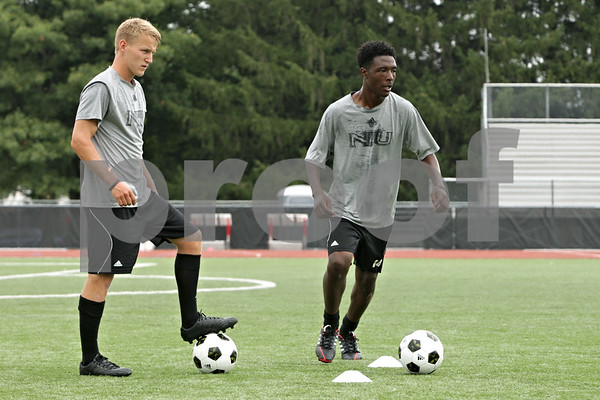 Rob Winner – rwinner@shawmedia.com<br /> <br /> Richard Hall (left) and Chris Bernard, both freshmen and from England, participate in a drill during a Northern Illinois University soccer practice in DeKalb Wednesday, Aug. 28, 2013.