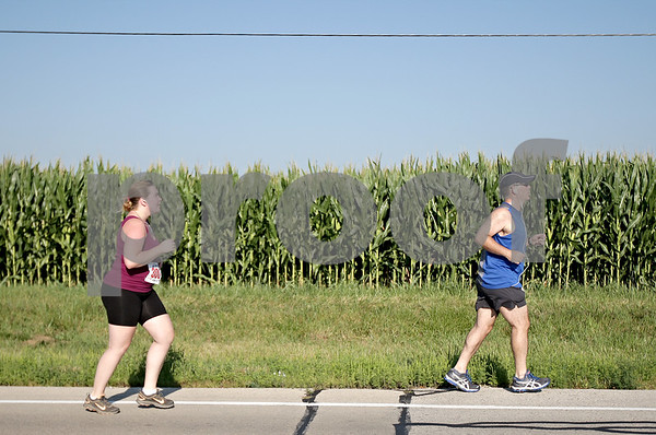 Monica Maschak - mmaschak@shawmedia.com<br /> Greg Snyder (right), of Dundee, and Stephanie Hunter, of Cortland, run among the corn fields at the annual Corn Classic 3 km and 10 km races on Saturday, August 24, 2013.