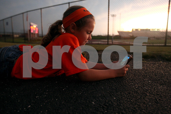Monica Maschak - mmaschak@shawmedia.com<br /> Ella Medina, 6, of DeKalb, plays a game on her phone as she waits out a lightning delay at Vernon Hills High School on Friday, August 30, 2013. Start time for the game was supposed to be 7:30 p.m.
