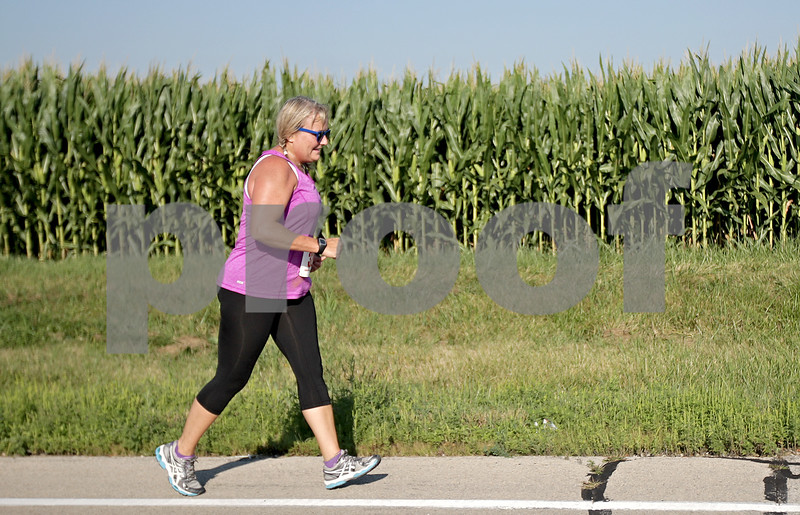 Monica Maschak - mmaschak@shawmedia.com<br /> Nanci Holtsford, from Texas, runs beside the corn fields at the annual Corn Classic 3 km and 10 km races on Saturday, August 24, 2013.