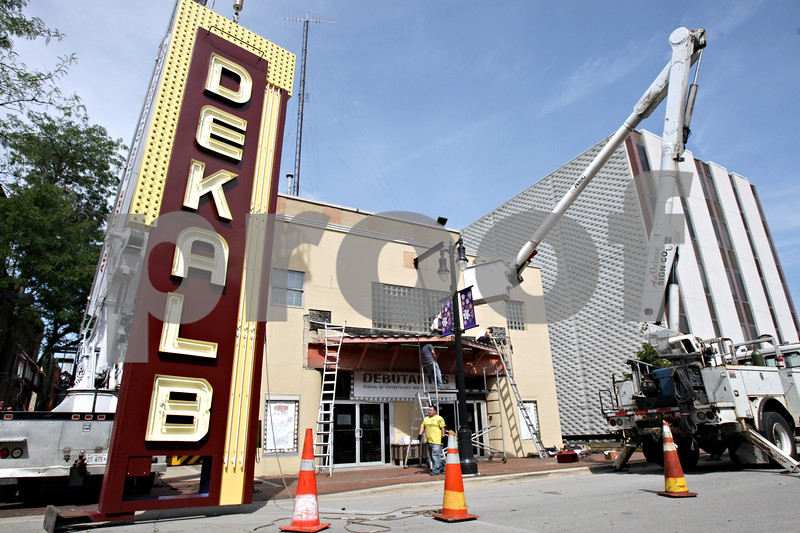 Rob Winner – rwinner@shawmedia.com<br /> <br /> Crews work to install the DeKalb Theater marquee Tuesday morning before tackling the on-site fabrication that's needed to finish restoring the sign at Debutantes School of Cosmetology and Nail Technology, 145 N. Third St. in DeKalb. The single-screen theater operated from 1949 to 1991 and has housed several businesses since then. The fully restored marquee will be showcased at a ceremony at 8:30 p.m. Thursday.