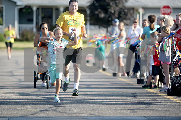 Monica Maschak - mmaschak@shawmedia.com<br /> Rachael Hartness, 9, raises her arms in excitement as she is followed by her father, Chris Hartness, in the final stretch at the annual Corn Classic 3 km and 10 km races on Saturday, August 24, 2013.