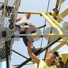 Rob Winner – rwinner@shawmedia.com<br /> <br /> Anthony Zukauski (top) and Kristie Porretta of Windy City Amusements assemble the Zipper ride in the Ellwood Parking Lot in DeKalb on Wednesday morning ahead of this weekend's Corn Fest. Zukauski has assembled and operated the ride for 12 years.
