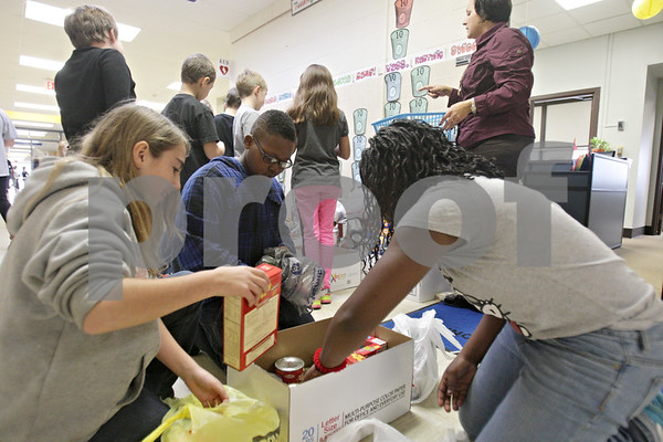 Rob Winner – rwinner@shawmedia.com<br /> <br /> On Tuesday morning, fifth grade students at Lincoln Elementary School in DeKalb, including (from left to right) Liz Wherman, 10, Eric Williams, 10, and Jacoya Bennett, 10, count food items that will be donated to the Freezing for Food annual food drive on Friday.<br /> <br /> Tuesday, Dec. 3, 2013