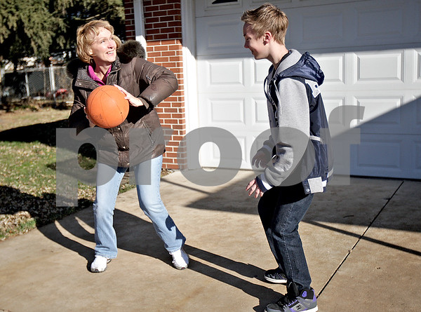 Monica Maschak - mmaschak@shawmedia.com<br /> Brandon Nikkila, 12, plays one-on-one basketball with his mother, Karen Nikkila in front of their Sycamore home on Saturday, November 23, 2013. Brandon is on the waiting list for a Big Brother match-up.