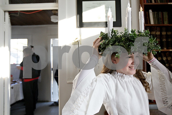 Monica Maschak - mmaschak@shawmedia.com<br /> Amanda Swedberg, 12, fixes the wreath atop her head during a holiday open house at the Old North Grove School in Sycamore on Saturday, November 30, 2013. Swedberg represented the Swedish St. Lucia and handed out straw ornaments to visitors.