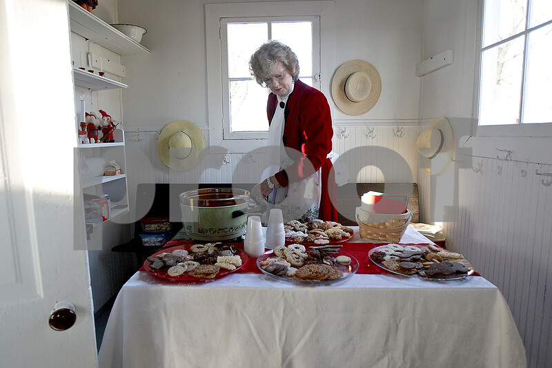 Monica Maschak - mmaschak@shawmedia.com<br /> Alice Whitney, member of the North Grove School Association, replenishes the cookies and cider during a holiday open house at the Old North Grove School in Sycamore on Saturday, November 30, 2013. Whitney attended the one-room school up until sixth grade.