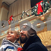 Rob Winner – rwinner@shawmedia.com<br /> <br /> Eleanor Burlingame, 3, and her father Jacob Burlingame of DeKalb listen to the madrigal singers of DeKalb High School inside the Egyptian Theatre while waiting for Santa Claus to arrive on Thursday, Dec. 5, 2013.