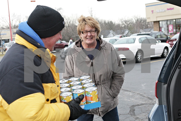 Rob Winner – rwinner@shawmedia.com<br /> <br /> Sue Snow of Sycamore drops off canned goods with1360 WLBK host Terry 'TD' Ryan during the Freezin' for Food 13th annual food drive in DeKalb on Thursday afternoon.
