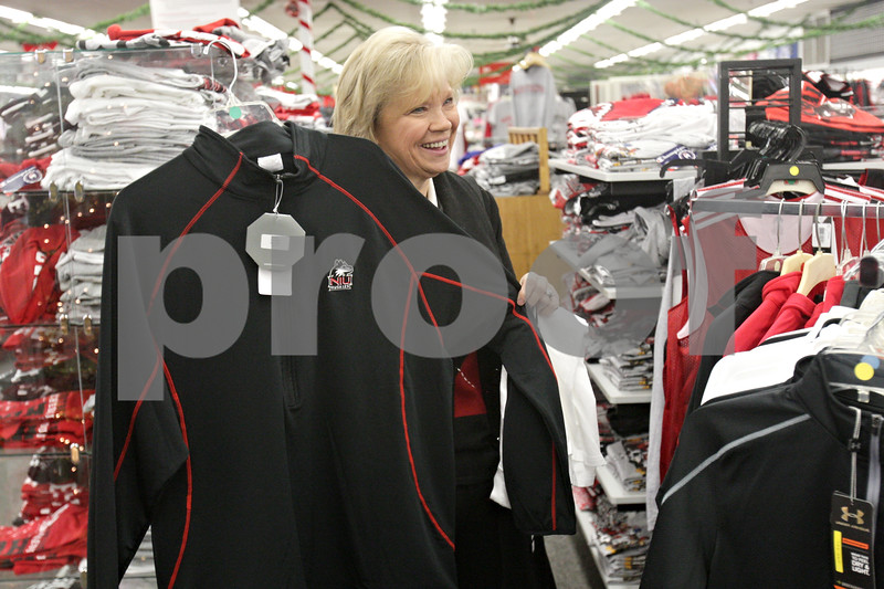 Rob Winner – rwinner@shawmedia.com<br /> <br /> Kim Phad of Planfield holds up a sweatshirt to show her husband, Jim Phad (not pictured), as the two shopped for Northern Illinois University apparel for their three children that graduated from NIU while at the Village Commons Bookstore in DeKalb on Tuesday, Dec. 3, 2013.