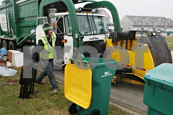Rob Winner – rwinner@shawmedia.com<br /> <br /> Daniel Mueller of Waste Management moves an article of trash so his truck can access a recycling bin within the Eden's Garden subdivision in DeKalb on Wednesday, Dec. 4, 2013.