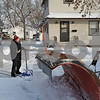 Rob Winner – rwinner@shawmedia.com<br /> <br /> DeKalb resident Connie Schorsch waits for a snow-plow truck to pass while shoveling her driveway on the 300 block of Fisk Avenue on Wednesday, Dec. 11, 2013.