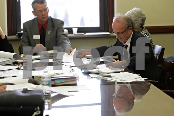 Rob Winner – rwinner@shawmedia.com<br /> <br /> Clay Campbell (right) hands a document to county clerk and recorder Doug Johnson during an Electoral Board hearing held for an objection of Campbell's candidacy made by Riley Oncken at the DeKalb County Courthouse in Sycamore, Ill., Friday, Dec. 13, 2013.