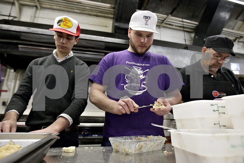 Monica Maschak - mmaschak@shawmedia.com<br /> Chef Alex Smith (center) prepares his pork rillette monte christo with smoked apple butter, pickled apple slices and gruyere during Battle of The Chefs at Feed 'Em Soup on Friday, December 13, 2013.