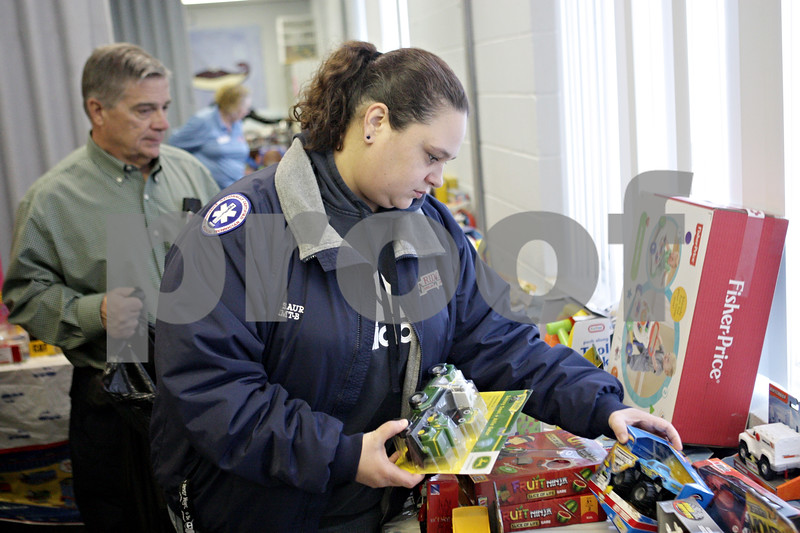Rob Winner – rwinner@shawmedia.com<br /> <br /> Evelyn Saur (front) of DeKalb looks over gifts while being assisted by Dick Dowen during the Marine Corps Toys for Tots distribution event at the Salvation Army in DeKalb, Ill., Tuesday, Dec. 17, 2013.
