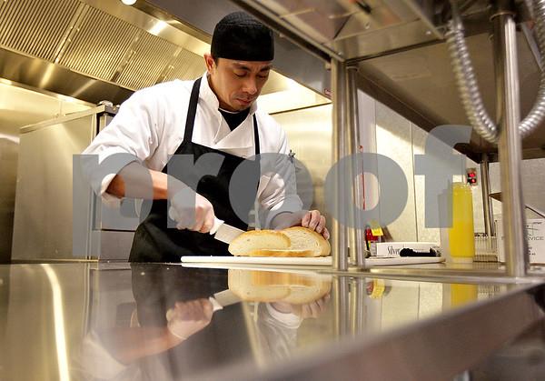 Monica Maschak - mmaschak@shawmedia.com<br /> Line cook Xan Peldonia slices bread in preparation for a holiday party at Faranda's in DeKalb on Saturday, December 14, 2013.