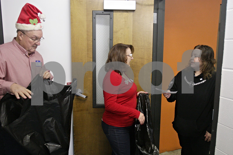 Rob Winner – rwinner@shawmedia.com<br /> <br /> (From left to right) John Clemetsen unfolds a bag as Sue Klopfenstein assists Karrie Pionke during the Marine Corps Toys for Tots distribution event at the Salvation Army in DeKalb, Ill., Tuesday, Dec. 17, 2013.