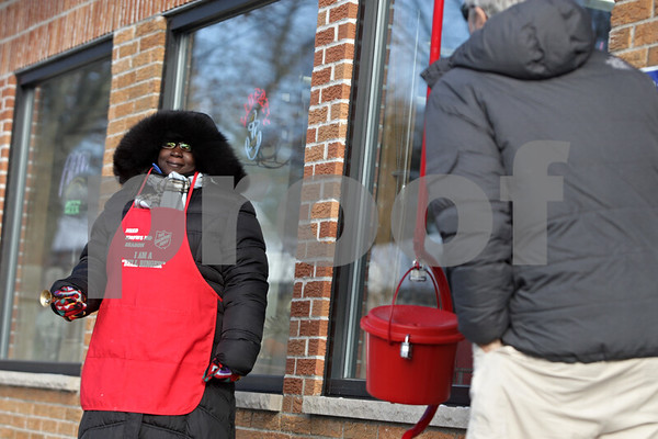Rob Winner – rwinner@shawmedia.com<br /> <br /> Treneice Nichols (left) of the Salvation Army rings a bell as a customer leaving Inboden's Meats Ltd. in DeKalb checks his pockets for a donation on Thursday, Dec. 12, 2013.
