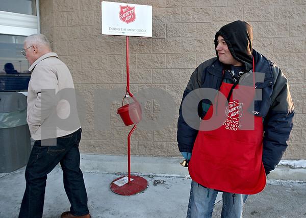 Monica Maschak - mmaschak@shawmedia.com<br /> Alex Vega, with the Salvation Army, greets customers walking into the DeKalb Walmart on Wednesday, December 11, 2013. The money donated to the Salvation Army around the holidays sustains the charitable organization year round.