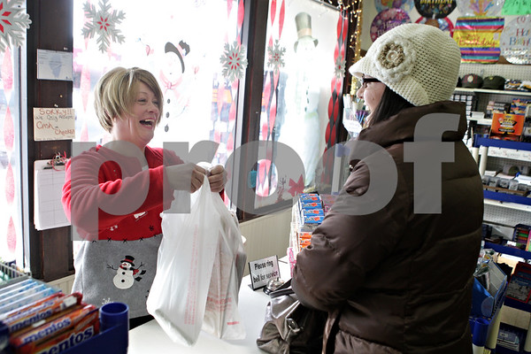Rob Winner – rwinner@shawmedia.com<br /> <br /> Jana Thomas a retail sales clerk at Super One Dollar Store in Sycamore helps Becki Burke of Sycamore with her purchases on Thursday, Dec. 12, 2013. Thomas has been working at the retail store for six weeks.